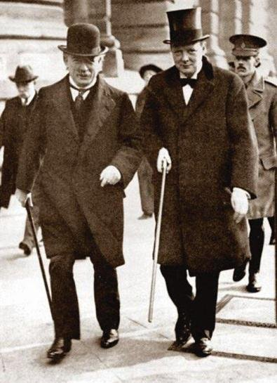 Churchill in top hat walking with Champberlain