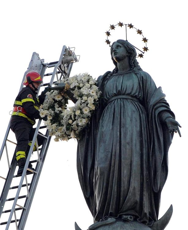 Firefighter places a wreath on the arm of Our Lady of the Immaculate Conception on her feast day in Rome, Italy