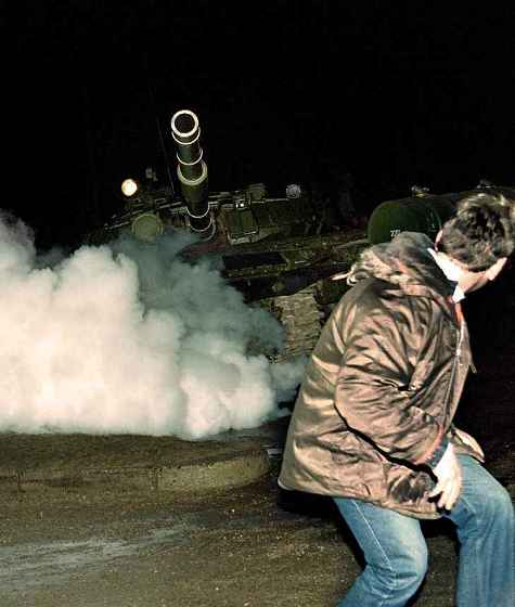 A Lithuanian flees a Soviet tank during the Russian invasion of Lithuania and occupation of Vilnius' radio and TV station, January 13, 1991