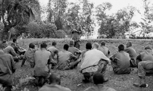 The Grunt Padre leads his men in prayer on the battlefield. Father Capodanno went into the jaws of danger to be with his men, anointing the dying and caring for the wounded.