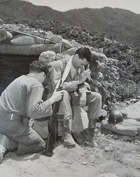 Chaplain Harold O. Prudell hears a soldier's confession on the front lines of Korea, June, 1951