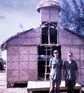 Father Capodanno (left) stands outside his makeshift chapel in Vietnam.