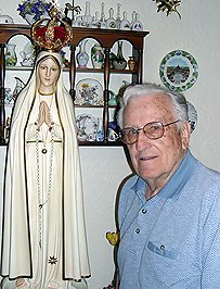 Mr. Norbert Arnold poses beside the Fatima statue of the TFP
