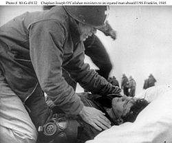 Fr. Joseph O'Callahan ministers to an injured man aboard the USS Franklin, March, 1945