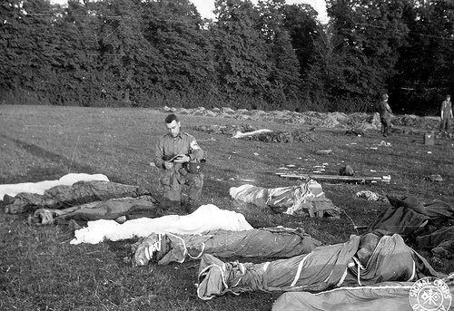 Fr. Francis L. Sampson giving Last Rites to paratroopers killed in action during the D-Day invasion of Normandy.
