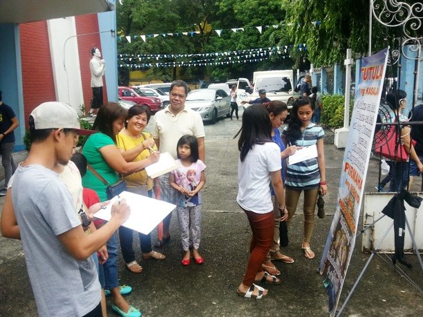 "Philippines — Parish families and youth sign the ""Filial Appeal to His Holiness Pope Francis"" at a Supplica Filiale stand."
